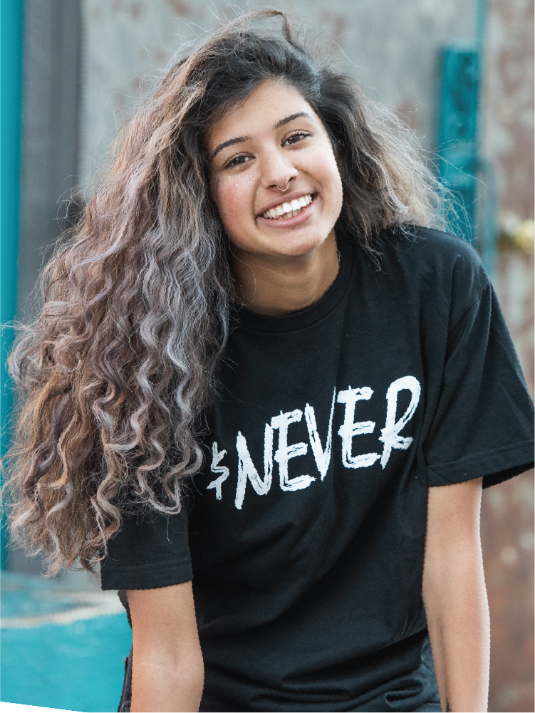 Young American female teenager with curly hair smiles at the camera while wearing an Exodus Road t shirt.