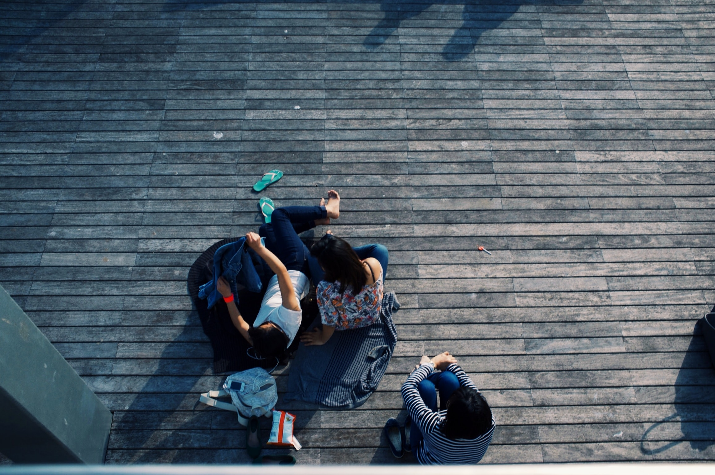 Overhead image of a group of teenagers sitting outside together.