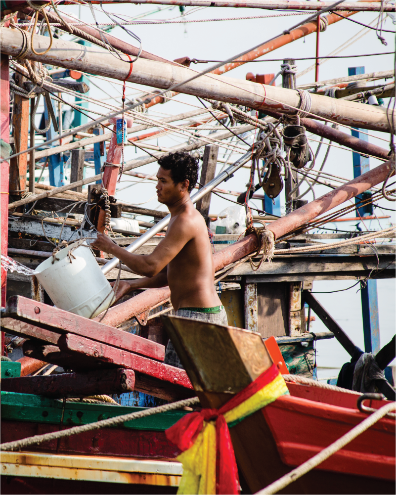 Shirtless SE Asian man carries a bucket while working on a boat.