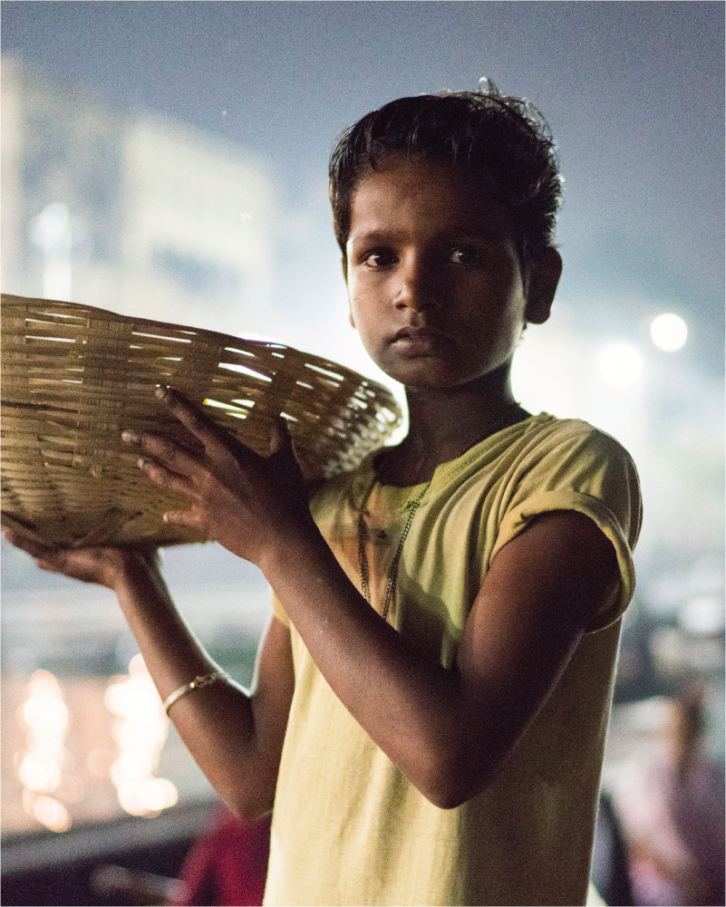 Young Indian boy walks through a street at night while carrying a basket on his shoulder.