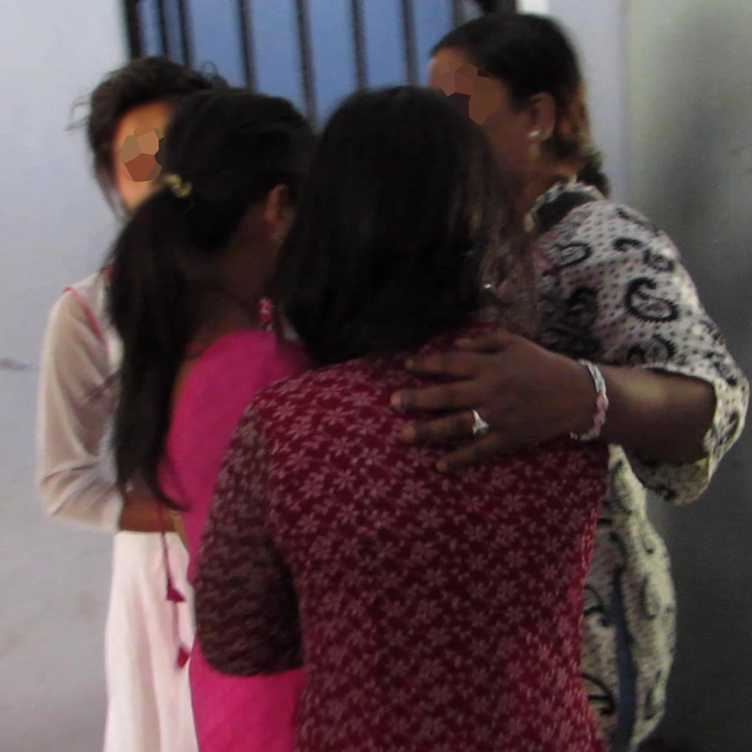 A social worker in India comforts three young female survivors of human trafficking.