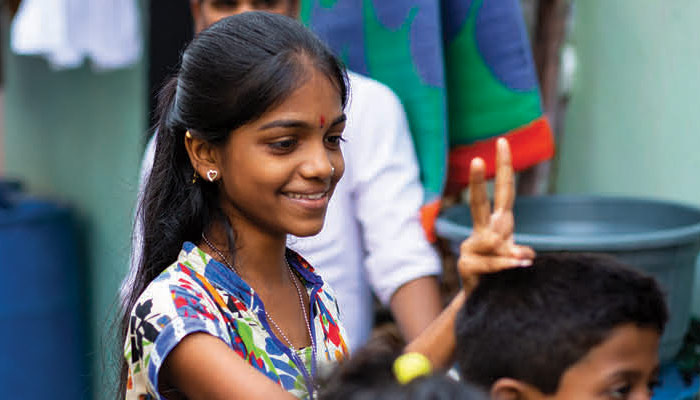 Young girl in India smiles and makes a peace sign with her fingers.