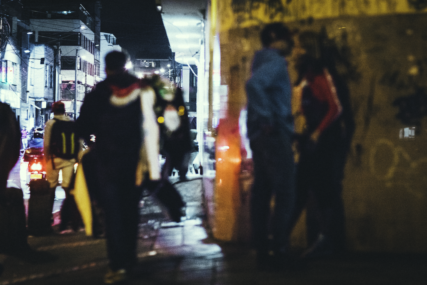 Man and woman approach each other in a dark corner of a Latin American street.