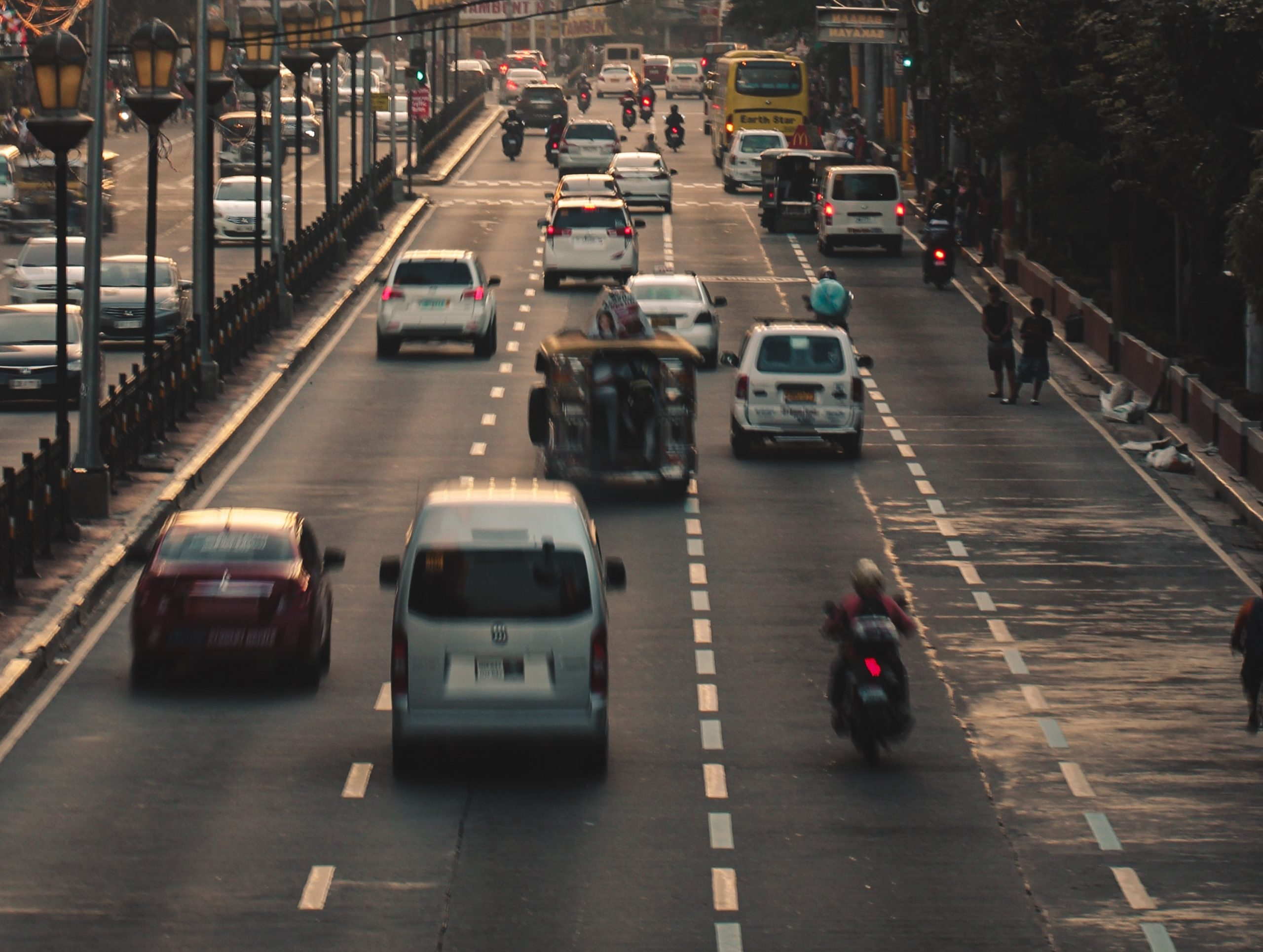 Cars and mopeds navigate four lanes of traffic on a busy stretch of Southeast Asian highway.